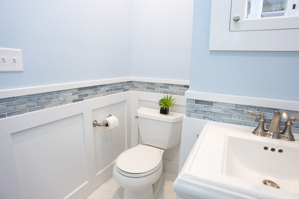 Small bathroom with hexagonal tile, pedestal sink, comfort height toilet, wainscot and accent tile