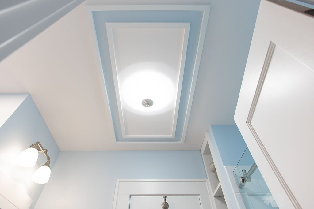 Overhead light surrounded by ceiling trim mirroring custom tile floor accent