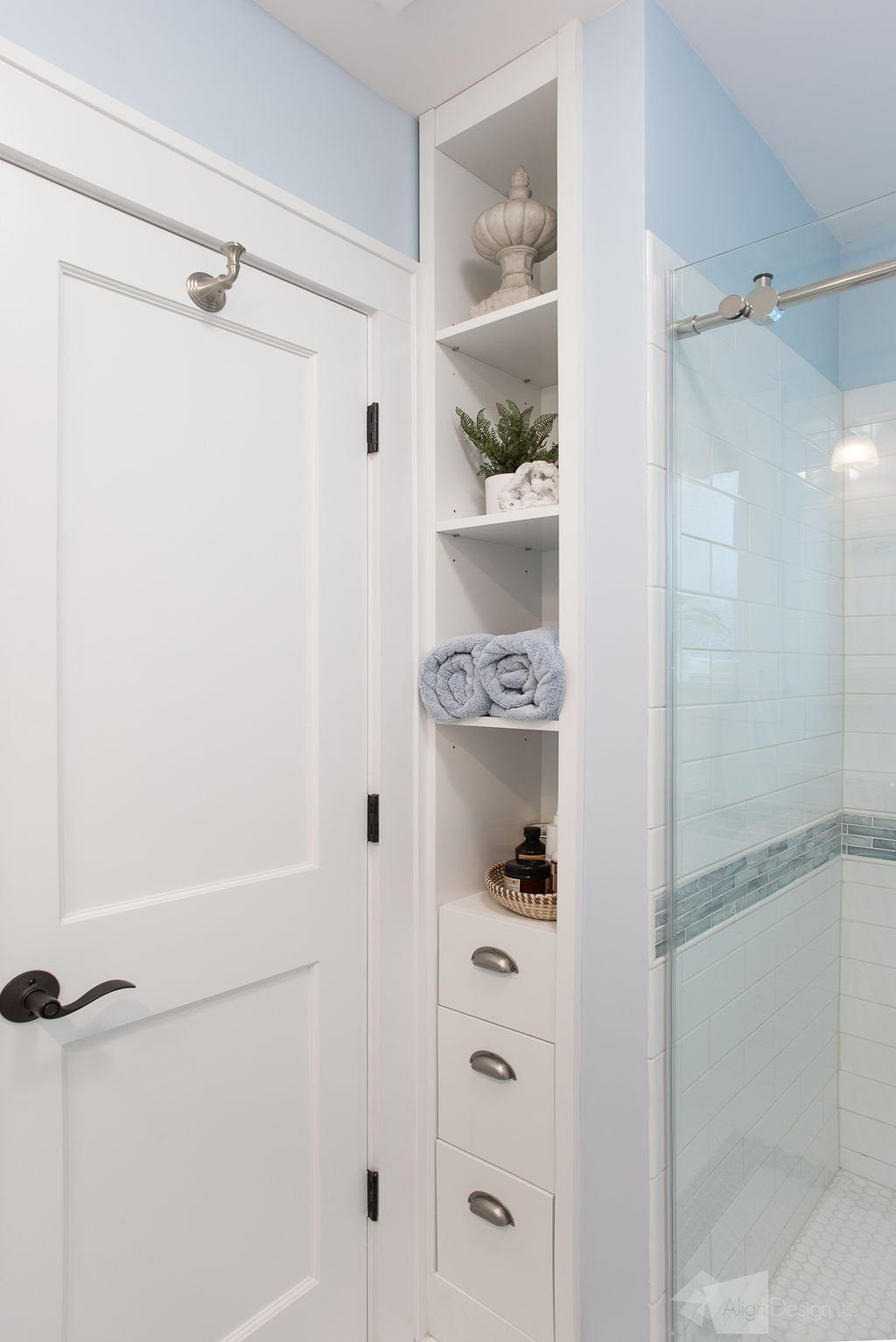 custom shower with glass shower door, custom cabinetry, robe hook and door knob