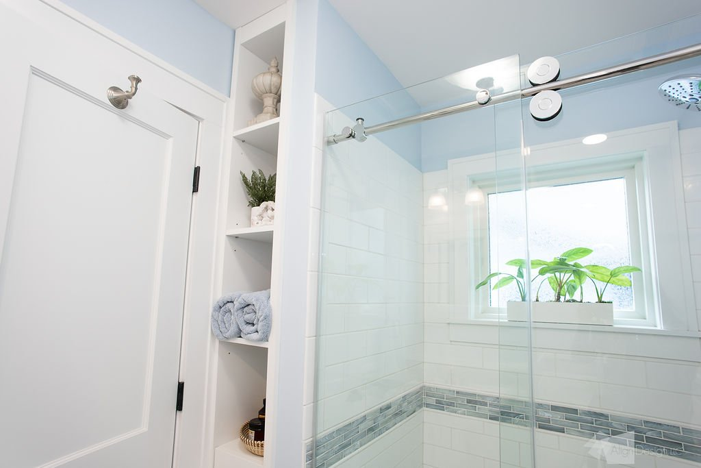 custom shower with glass shower door, custom cabinetry, robe hook, obscured glass window, pvc window trim